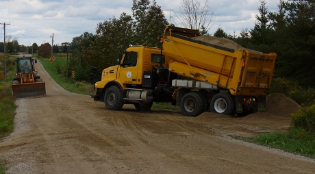 Dump truck and bulldozer adding stone chip surface to trail